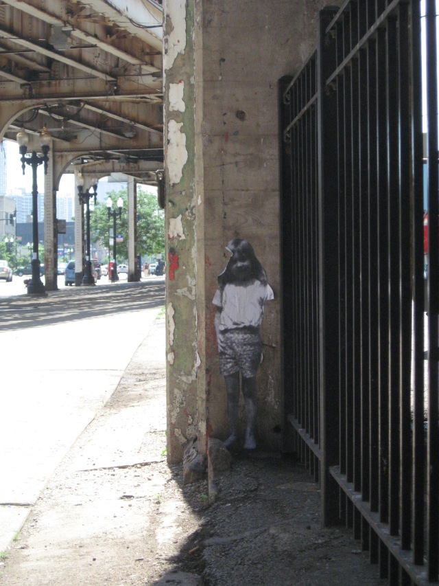 A street artist pasted several of these ghost-like images on the old concrete supports.