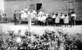 """Floyd Brown (standing, left of porch), with friends and students in front of the first school building of the Fargo Agricultural School in Monroe County, 1920."" Courtesy of the Arkansas History Commission."